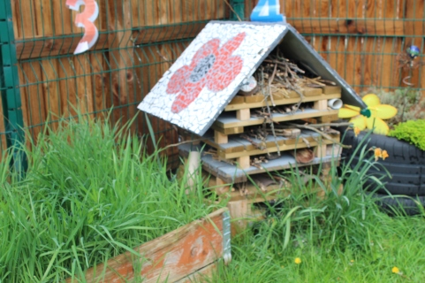 Giant Bug House with a mosaic roof, filled by children at Sure Start centre