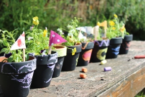 Painted pots planted with pansies, with handmade flags and chalked designs.